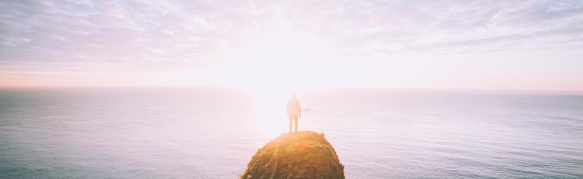 Hombre en una montaña mirando al mar