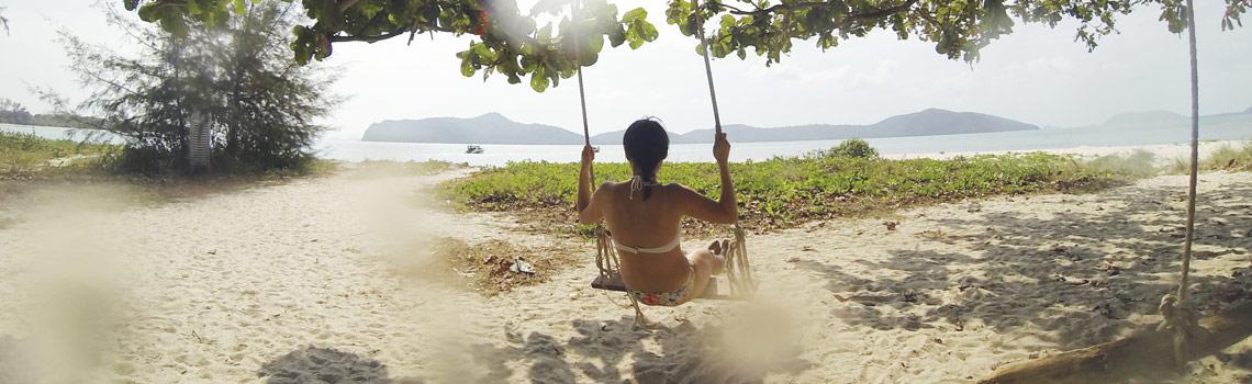 Mujer en columpio en la playa