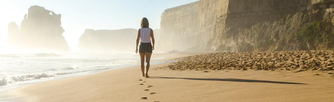 Mujer en la playa con acantilado